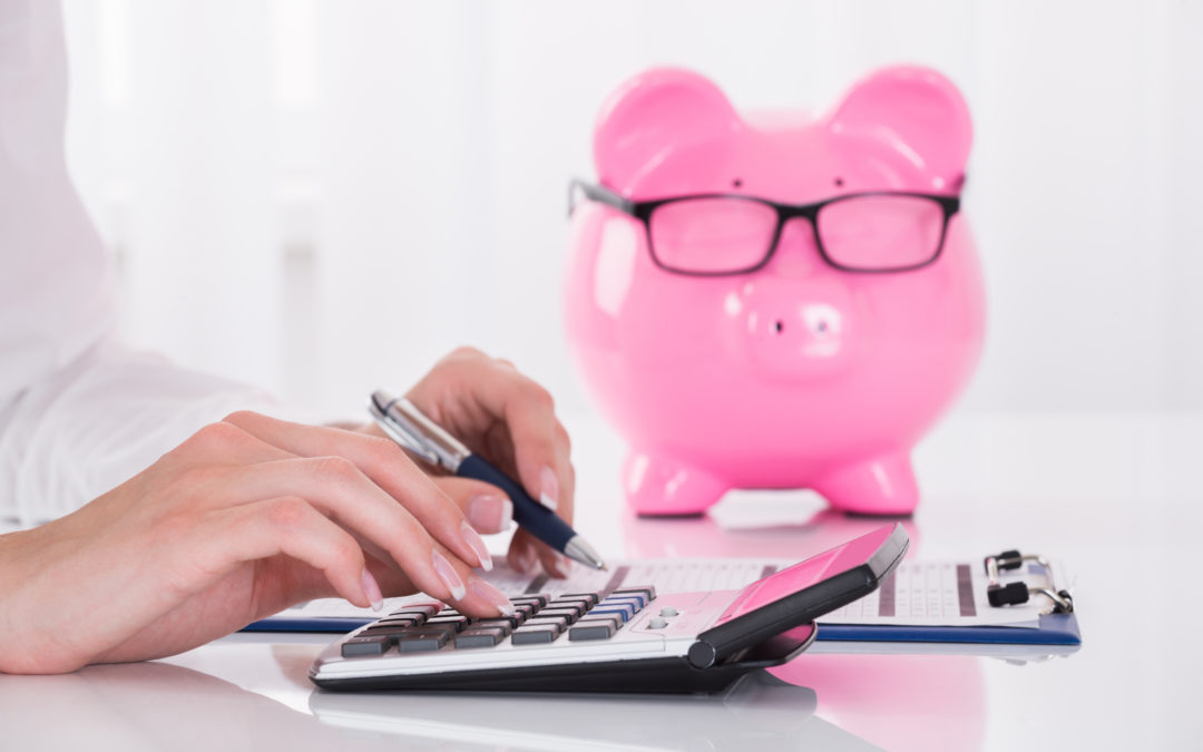 Person typing on calculator with piggy bank